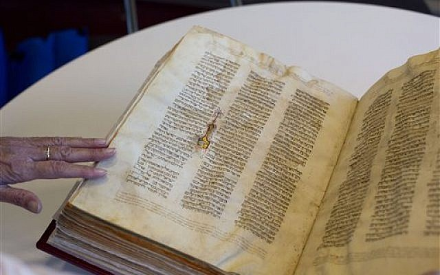 In this October 5, 2014, photo, a library official shows a Jewish manuscript smuggled into Israel from Damascus in a Mossad spy operation in the early 1990s, in Jerusalem. (photo credit: AP/Sebastian Scheiner, File)