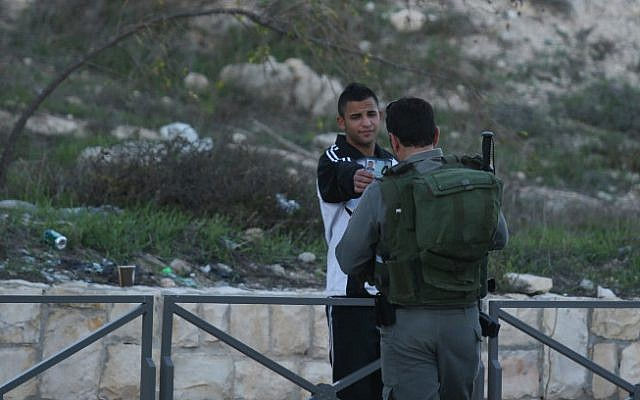 A Border Policeman checking the papers of an Israeli Arab resident of Jabel Mukaber on November 19, 2014 (photo credit: Nati Shohat/ Flash 90)