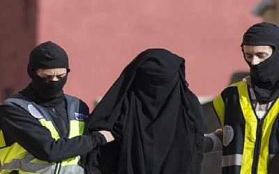 Spanish police escort a 20-year-old Abaya clad woman in Melilla on December 16, 2014 during the combined arrests of seven people in Spain and Morocco for allegedly recruiting young women via the Internet to join the jihadist Islamic State group fighting in Iraq and Syria. (AFP)