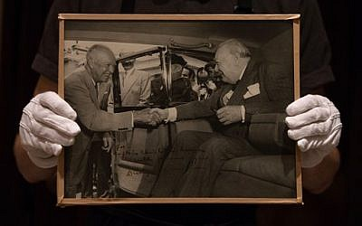"In this photo taken Tuesday, Dec. 9, 2014, a member of Sotheby's staff poses for a picture with a photograph of U.S. President Dwight D. Eisenhower and Churchill with dedication: ""for Christopher Soames, with personal regards, Dwight Eisenhower"" at the auction house in London, England. (photo credit: AP Photo/Tim Ireland)"