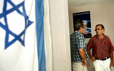 Illustrative: An Israeli flag hangs on the wall of the Jewish Community Center in Havana, Cuba, where two men are speaking on August 1, 2004. (Serge Attal/Flash90)