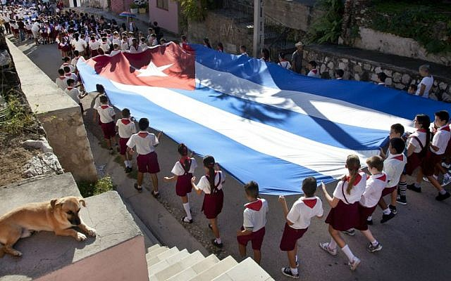 Young students carry a large Cuban flag, as they attend a parade through the streets of Gibara, Cuba. January 20, 2014. (photo credit: Moshe Shai/Flash90)