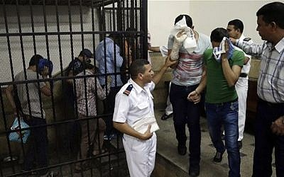 "Illustrative: Eight Egyptian men convicted for ""inciting debauchery"" following their appearance in a video of an alleged same-sex wedding party on a Nile boat leave the defendant's cage in a courtroom in Cairo, Egypt, November 1, 2014. (AP/Hassan Ammar, File)"
