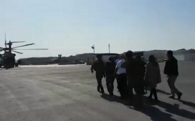 Magen David Adom and army personnel use an IDF helicopter to evacuate a Palestinian infant to an Israeli hospital on December 27, 2014. (screen capture: YouTube/Ynet)