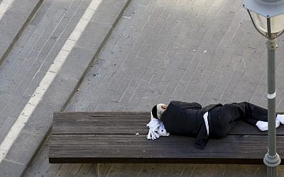 Illustrative photo of a man sleeping on a bench in the center of Jerusalem November 9, 2014. (Photo credit: Nati Shohat/FLASH90)