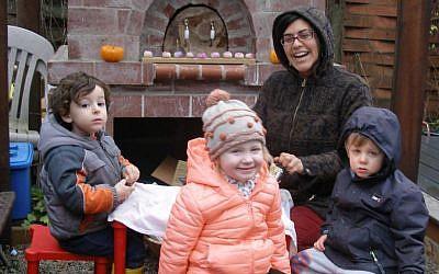 Sarabel Eisenfeld, the founder of Gan Shalom, and her Portland Jewish preschoolers grating potatoes outside for Hanukkah latkes. (Anthony Weiss/JTA)