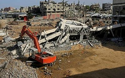A Palestinian crane removes the rubble of the Jamal Abdelnaser UNRWA School in Shejaiya, a neighborhood in Gaza City, in the northern Gaza Strip, December 3, 2014. (photo credit: AP/Adel Hana)