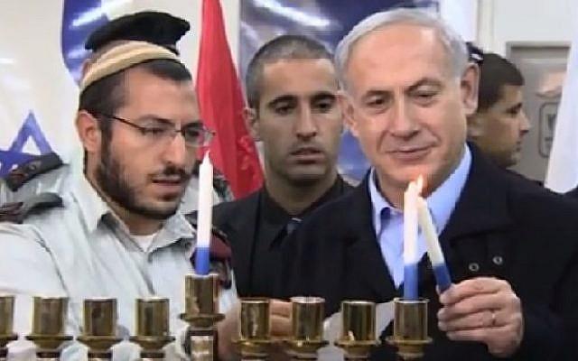 Prime Minister Benjamin Netanyahu lights the first candle of Hanukkah, December 16, 2014. (Screenshot: YouTube/GPO)