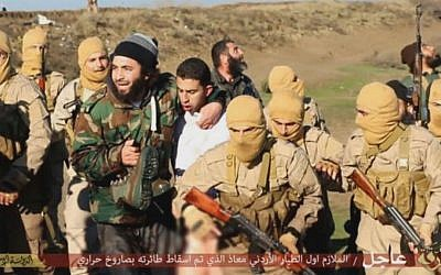 A picture released by the Islamic State purporting to show members of the group holding a captive Jordanian pilot. Wednesday, December 24, 2014 (screen capture: YouTube)