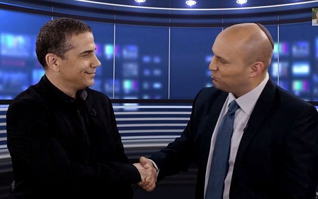 Journalist Yinon Magal (L) shakes hands with Jewish Home Party leader Naftali Bennett (R) after declaring his intention to join the party, December 27, 2014. (screen capture: YouTube/Naftali Bennett)