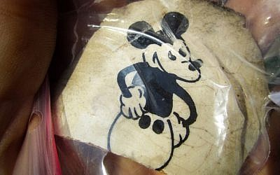Fragment of a ceramic cup excavated at the former Nazi death camp Sobibor, with an image of Mickey Mouse. The artifact was unearthed by archeologists Wojtek Mazurek and Yoram Haimi in 2014 (Matt Lebovic/The Times of Israel).
