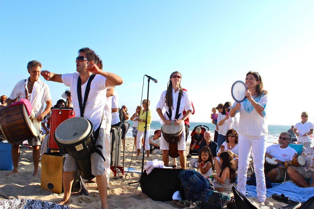 Rabbi Naomi Levy and the Nashuva band drum playing on the beach (Phyllis Osman/JTA)
