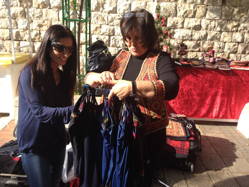 Maisoon Zoabi choosing hand-embroidered tanktops (photo credit: Jessica Steinberg/Times of Israel)