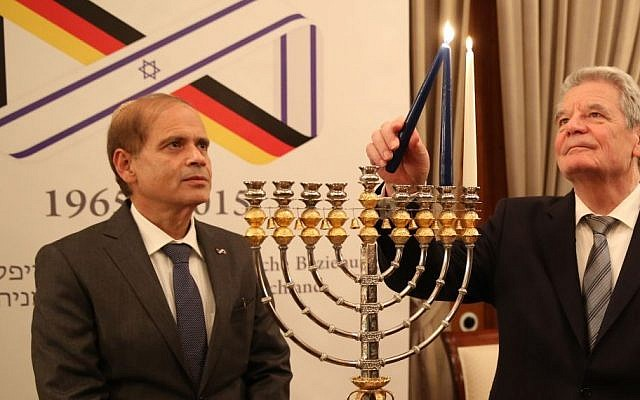 Illustrative: Israeli Ambassador to Germany Yakov Hadas-Handelsman watches as German President Joachim Gauck lights a menorah during a ceremony to mark 50 years of ties between Israel and Germany on December 18, 2014. (photo credit: Ministry of Foreign Affairs)