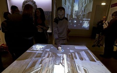 An interactive table shows a reconstruction of the Old Ghetto during its unveiling for the press in Rome's Jewish Museum, December 4, 2014. (photo credit: AP/Alessandra Tarantino)