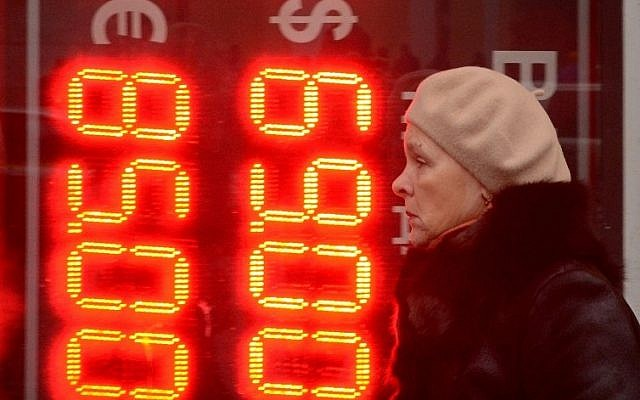 A woman walks past a board listing foreign currency rates against the Russian ruble outside an exchange office in central Moscow on December 16, 2014. (Photo credit: AFP/ Kirill Kudryavtsev)