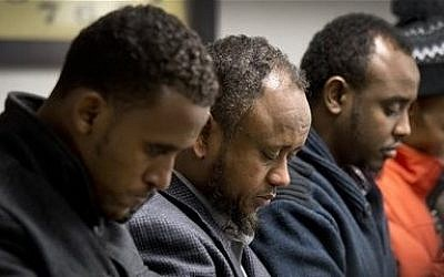 Men gather to pray the day after 15-year-old Abdisamad Sheikh-Hussein was struck and killed by a hit-and-run driver in front of the Somali Center of Kansas City, Mo., Friday, Dec. 5, 2014. (photo credit: AP Photo/The Kansas City Star, Keith Myers)