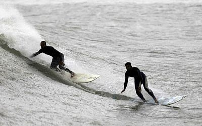 In this Thursday, November 27, 2014 photo, Palestinians Mohammed Abu Jayyab, 41, and Ahmed Abu Hasira, 35, surf on the beach of Gaza City. (photo credit: AP Photo/Khalil Hamra)