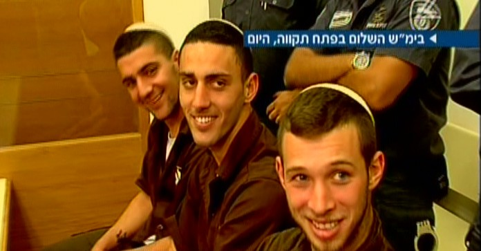 The three suspects in the arson attack on a Jewish-Arab school in Jerusalem smile at photographers in the Petah TIkvah Magistrate's Court on Thursday, December 11, 2014 (screen capture: Channel 2)