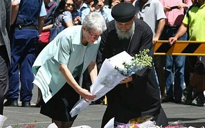 People lay flowers to pay respect to the shooting victims at a makeshift memorial in Sydney, Australia, on December 16, 2014 (photo credit: AP/Photo/Steve Christo)