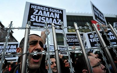 "Staff members and supporters of Zaman newspaper shout slogans and hold placards reading ""Free press can not be silenced"" during a protest against a raid by counter-terror police in Istanbul on December 14, 2014 (photo credit: Ozan Kose / AFP)"