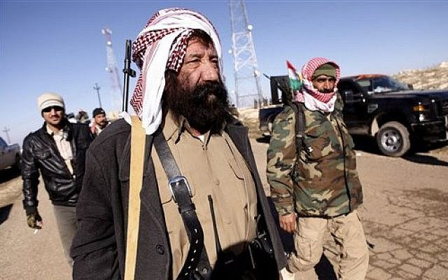 Yazidi fighters head to battle Islamic State militants, on the summit of Mount Sinjar, in Iraq, Sunday, Dec. 21, 2014. (Photo credit: AP/Dalton Bennett)