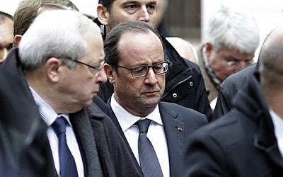 French President Francois Hollande (C) arrives at the headquarters of the French satirical newspaper Charlie Hebdo in Paris on January 7, 2015, after armed gunmen stormed the offices leaving eleven dead, including two police officers, according to sources close to the investigation. (photo credit: AFP/KENZO TRIBOUILLARD)