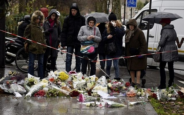 Floral tributes are laid on the ground during a minutes silence in Paris on January 8, 2015, a day after Islamist gunmen killed 12 people in an attack on the offices of satirical magazine Charlie Hebdo. (photo credit: AFP/ MARTIN BUREAU