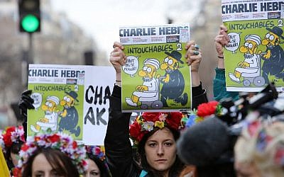 "Femen activists hold Charlie Hebdo frontpages during a Unity rally ""Marche Republicaine"" on January 11, 2015 at the Place de la Republique (Republique's square) in Paris in tribute to the 17 victims of a three-day killing spree by homegrown Islamists. (photo credit: AFP/LOIC VENANCE)"