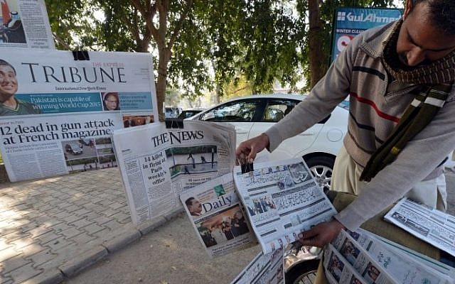 A Pakistani vendor arranges morning newspapers with front-page-coverage of the attack by gunmen on French satirical weekly Charlie Hebdo in Paris, at a roadside newsstand in Islamabad on January 8, 2015. (photo credit: AFP/Aamir QURESHI)