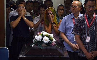 Family members of Hayati Lutfiah Hamid, first identified victim of the ill-fated Malaysian air carrier AirAsia flight QZ8501, cry upon receiving her remains at the police hospital in Surabaya on January 1, 2015. (photo credit: AFP PHOTO / MANAN VATSYAYANA)