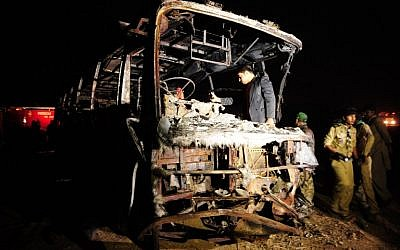Pakistani volunteers search for victims inside a burnt out passenger bus after it collided with an oil tanker along the Super Highway near Karachi early on January 11, 2015. (photo credit: AFP/Asif HASSAN)