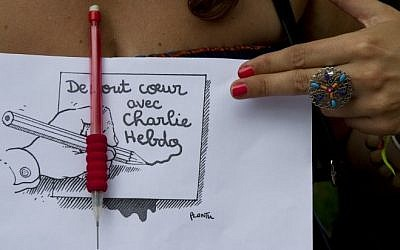 A woman holds a sign showing a cartoon by Plantu, outside the French Embassy in Buenos Aires on January 7, 2015, during a demonstration against the attack by gunmen in the offices of the satirical weekly Charlie Hebdo in Paris. (Photo credit: AFP/ALEJANDRO PAGNI)