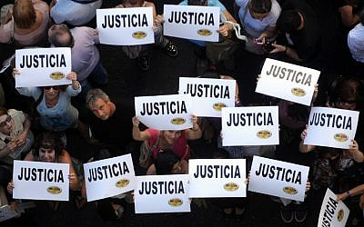 """Citizens hold placards that read """"Justice"""" during a rally in front of the headquarters of the AMIA (Argentine Israelite Mutual Association), in Buenos Aires on January 21, 2015."""
