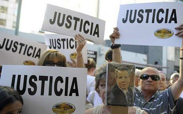 """People hold placards that read """"Justice"""" during a rally in front of the headquarters of the AMIA (Argentine Israelite Mutual Association), in Buenos Aires on January 21, 2015. (photo credit: Alejandro Pagni/AFP)"""