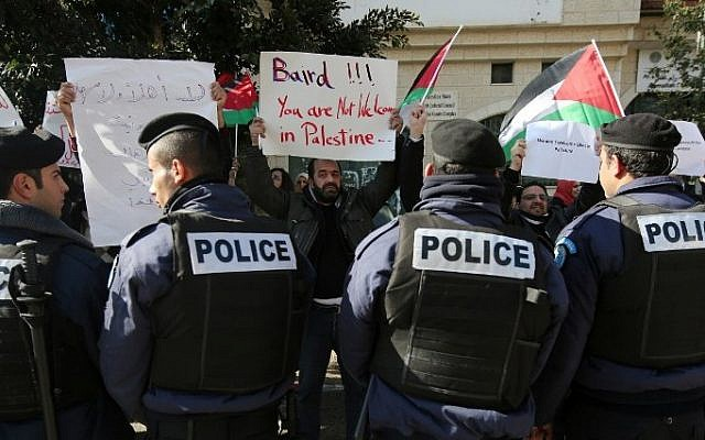 Policemen stand guard in front of Palestinian protesters holding placards before a meeting between Palestinian Authority Minister of Foreign Affairs Riyad al-Maliki and his Canadian counterpart John Baird on January 18, 2015, Ramallah. (AFP/ABBAS MOMANI)