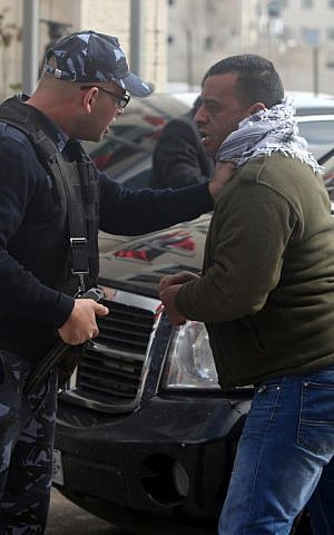 A Palestinian policeman stops a protester after angry Palestinian youths hurled eggs at the motorcade of Canadian Foreign Minister John Baird in Ramallah on Sunday, January 18, 2015 (photo credit: AFP/ABBAS MOMANI)
