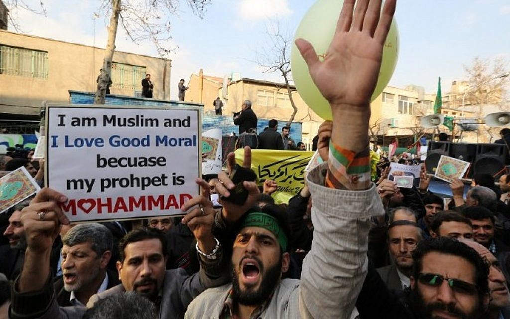 "Iranians take part in a protest against the printing of satirical sketches of the Prophet Muhammad by French satirical weekly Charlie Hebdo on January 19, 2015 outside the French embassy in Tehran. The demonstration was in response to a cartoon published in the latest issue of Charlie Hebdo showing on its cover the prophet Mohammed holding a ""Je Suis Charlie"" (I am Charlie) sign under the headline ""All is forgiven"", a week after a January 7 attack at its Paris headquarters killed 12 people. (photo credit: Atta Kenare/AFP)"
