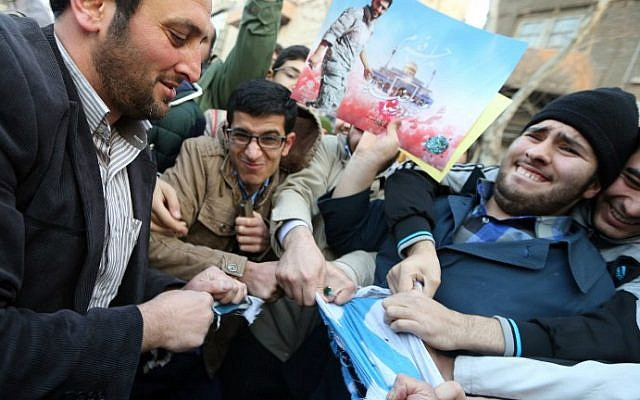 Iranian students tear an Israeli flag during a protest against the printing of satirical sketches of the Prophet Mohammed by French satirical weekly Charlie Hebdo, January 19, 2015 outside the French embassy in Tehran. (AFP/ATTA KENARE)