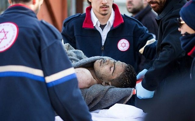 Medics transport a Palestinian man on a gurney who stabbed and wounded over a dozen passengers in an attack on a Tel Aviv bus on January 21, 2015 (photo credit: AFP/OREN ZIV)