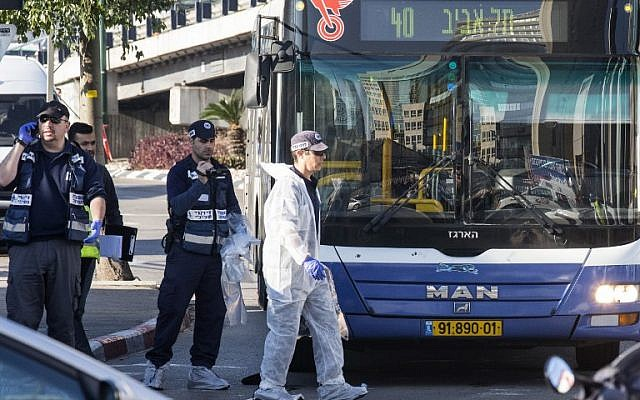 Israeli forensics examine the scene of an attack after a Palestinian man stabbed several people on a Tel Aviv bus on January 21, 2015. (photo credit:AFP/JACK GUEZ)