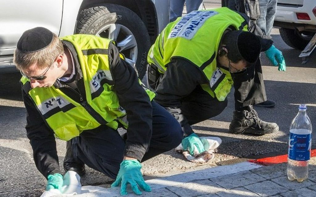 Israeli emergency services personnel clean the sidewalk at the scene of an attack after a Palestinian man stabbed several people on a Tel Aviv bus on January 21, 2015. (photo credit: AFP/JACK GUEZ)