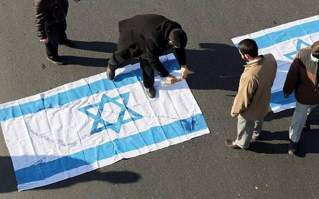 Illustrative: Iranian protesters pour kerosene on an Israeli flag during the funeral procession of Brigadier General Mohammad Ali Allahdadi in Tehran on January 21, 2015. (AFP/Atta Kenare)