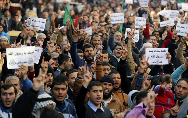 Palestinians hold placards and shout slogans praising Islam's Prophet Muhammad during a demonstration organized by Islamist movement Hamas against the cover cartoon of the Prophet published by French satirical magazine Charlie Hebdo, on January 23, 2015 in Jabaliya refugee camp in the northern Gaza Strip (photo credit: AFP/MOHAMMED ABED)