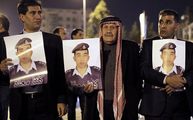 """Relatives of Jordanian air force pilot Moaz al-Kasasbeh, who crashed in Syria with a F-16 last month, carry posters with his portrait and a slogan reading in Arabic, """"we are all Moaz"""", during a protest near the Prime Minister office in Amman late on January 27, 2015 demanding the release of Sajida al-Rishawi, an Iraqi female suicide bomber on death row in Jordan . (photo credit: AFP PHOTO / KHALIL MAZRAAWI)"""