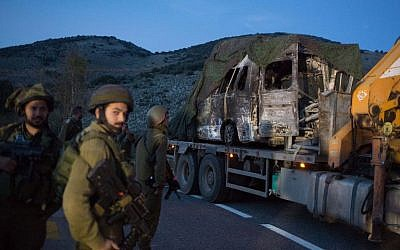 Israeli soldiers look at a burned-out vehicle loaded onto the back of a truck near Ghajar after it was removed from the seen of a Hezbollah missile attack along the Israel-Lebanon border on January 28, 2015. (photo credit: AFP/MENAHEM KAHANA)