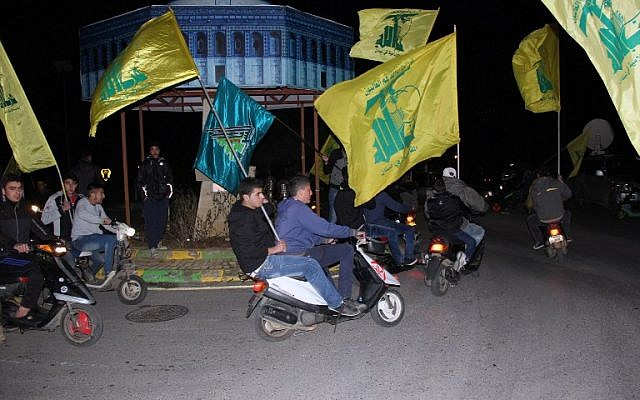Lebanese Hezbollah supporters wave the movement's flag in the village of Kfar Kila in southern Lebanon, near the Lebanon-Israel border on January 28, 2015. (photo credit:AFP/ALI DIA)
