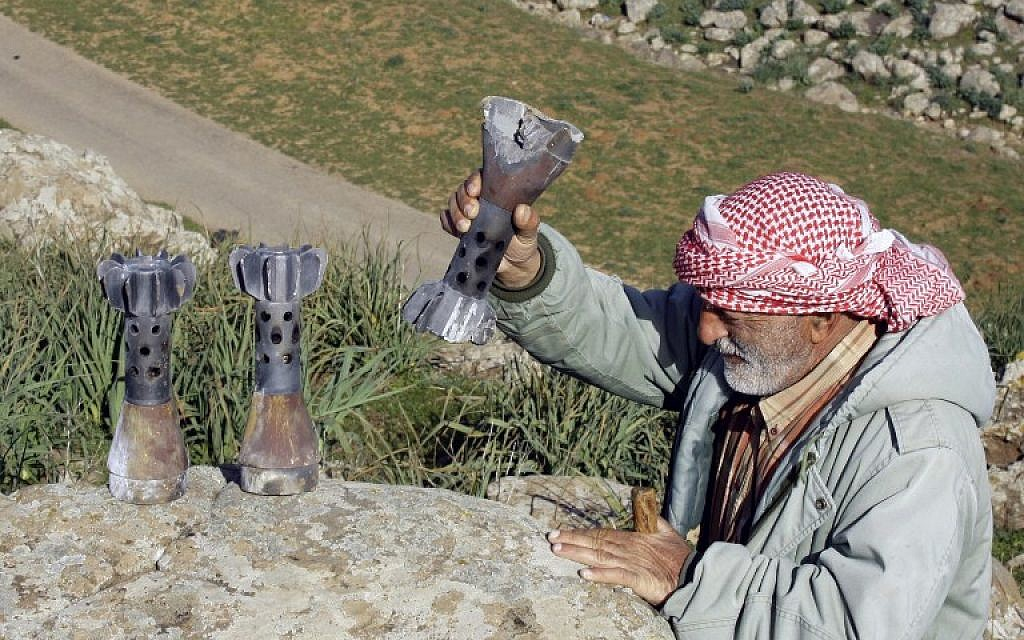 A Lebanese farmer puts in a line mortar shells collected from a field in the Lebanese village of al-Wazzani near the divided village of Ghajar along the Lebanese-Israeli border on January 29, 2015. (photo credit: AFP/MAHMOUD ZAYYAT)
