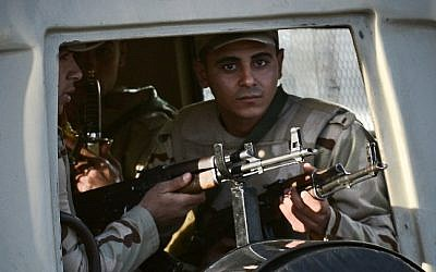 Egyptian members of the armed forces patrol outside al-Maza military airport where the bodies of the members of security forces, who were killed in North Sinai province during an attack the day before, had been flown on January 30, 2015 in the capital Cairo. (Photo credit: AFP/ MOHAMED EL-SHAHED)