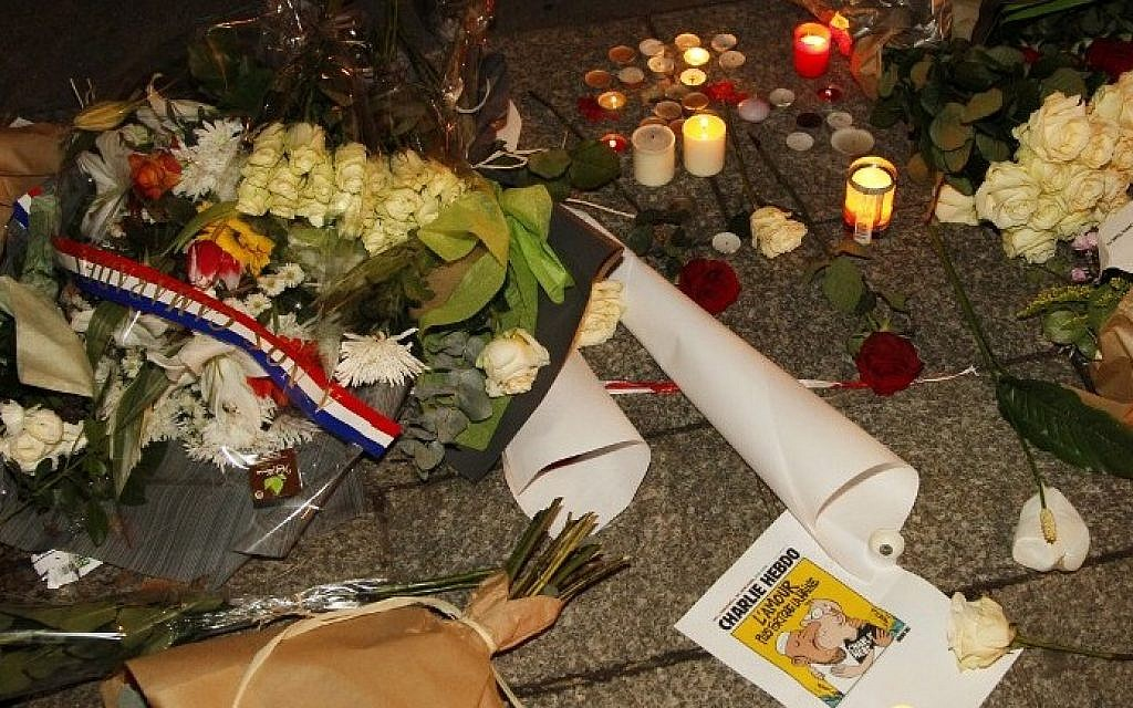 Flowers, candles and a picture of the front page of an edition of Charlie Hebdo laid out on the pavement near the offices of French satirical weekly Charlie Hebdo in Paris on January 7, 2015. (AFP/MATTHIEU ALEXANDRE)